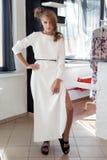 Mujer joven atractiva hermosa en vestido blanco de moda hermoso en el estudio que presenta para el lanzamiento de la moda de la c Foto de archivo libre de regalías