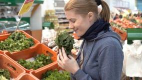 Mujer joven atractiva hermosa que escoge el verdor fresco en supermercado Concepto sano de la consumición almacen de metraje de vídeo