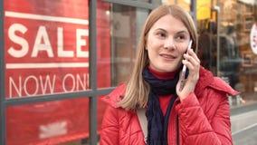 Mujer joven atractiva hermosa que habla con el amigo cerca de tienda de ventana Abrigo de invierno rojo Muestras de las ventas almacen de video
