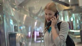 Mujer joven atractiva hermosa que habla con el amigo de la cabina de teléfono público Terminal de aeropuerto metrajes