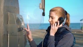 Mujer joven atractiva hermosa que habla con el amigo de la cabina de teléfono Puesta del sol del terraplén almacen de video