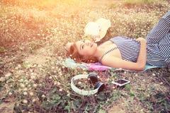 Mujer joven atractiva hermosa que miente acercando al auricular en la flor Fotos de archivo