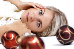 Mujer joven atractiva hermosa que miente en el piso con las bolas de la Navidad Fotografía de archivo