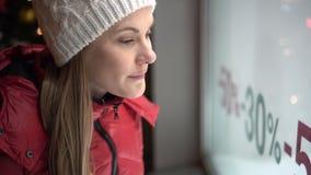 Mujer joven atractiva hermosa que mira la ventana de la tienda Abrigo de invierno rojo Muestras de las ventas Noche de la tarde almacen de metraje de vídeo