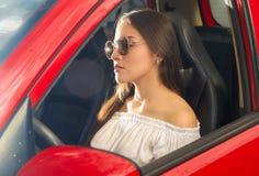 Mujer joven atractiva hermosa que presenta para la cámara y que lleva una blusa blanca mientras que el sol está reflejando sobre  Fotografía de archivo libre de regalías