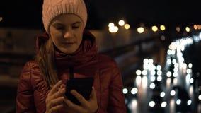 Mujer joven atractiva hermosa que se coloca en un puente y que usa su smartphone La ciudad enciende los coches almacen de metraje de vídeo