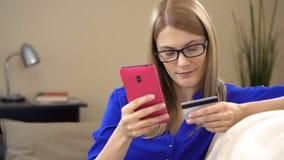 Mujer joven atractiva hermosa que se sienta en el sofá y que compra en línea con la tarjeta de crédito en un smartphone metrajes