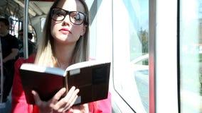 Mujer joven atractiva hermosa que sostiene el libro que se sienta en la tranvía, mirando la cámara almacen de video