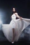 Mujer joven atractiva hermosa Retrato de la muchacha en el vestido blanco largo, estilo místico, misterioso, fondo oscuro Fotografía de archivo