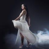 Mujer joven atractiva hermosa Retrato de la muchacha en el vestido blanco largo, estilo místico, misterioso, fondo oscuro Fotos de archivo