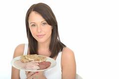 Mujer joven atractiva natural feliz sana que sostiene una placa de la comida fría fría del estilo noruego Fotografía de archivo libre de regalías