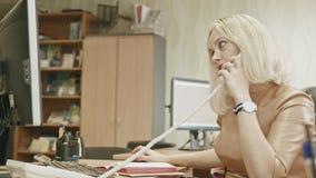 Mujer joven atractiva - oficina encantadora que trabaja contestando al teléfono en su oficina delante del ordenador, tiro del res almacen de video