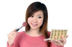 Mujer joven atractiva que aplica blusher Imagen de archivo