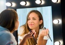 Mujer joven atractiva que aplica su maquillaje Fotografía de archivo libre de regalías