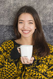Mujer joven atractiva que bebe una taza de té caliente Imágenes de archivo libres de regalías