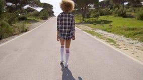 Mujer joven atractiva que camina abajo de un camino en la puesta del sol metrajes