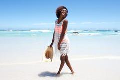 Mujer joven atractiva que camina en agua por la playa Foto de archivo libre de regalías