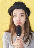 Mujer joven atractiva que canta con el micrófono Fotos de archivo