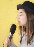 Mujer joven atractiva que canta con el micrófono Imágenes de archivo libres de regalías