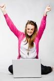Mujer joven atractiva que celebra con la computadora portátil Imagen de archivo