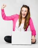 Mujer joven atractiva que celebra con la computadora portátil Imagenes de archivo