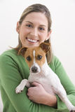 Mujer joven atractiva que celebra un perro y una sonrisa Imagen de archivo
