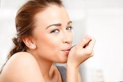 Mujer joven atractiva que come el yogur Fotografía de archivo libre de regalías