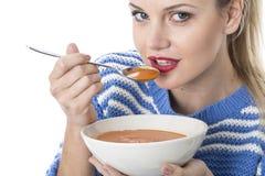 Mujer joven atractiva que come la sopa del tomate Fotografía de archivo libre de regalías