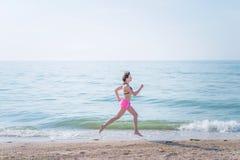 Mujer joven atractiva que corre en la playa imagenes de archivo