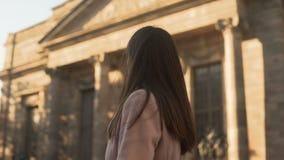 Mujer joven atractiva que da vuelta a la cámara, colocándose cerca de campus universitario metrajes