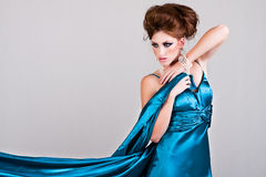 Mujer joven atractiva que desgasta una alineada azul del satén Imágenes de archivo libres de regalías
