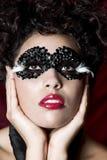 Mujer joven atractiva que desgasta una máscara negra de la gema Fotografía de archivo