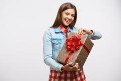 Mujer joven atractiva que destapa la actual caja que parece alegre y la sonrisa Fotografía de archivo libre de regalías
