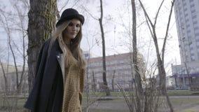 Mujer joven atractiva que disfruta de su tiempo afuera en parque con puesta del sol acci?n Mujer joven hermosa en sombrero que ca almacen de metraje de vídeo
