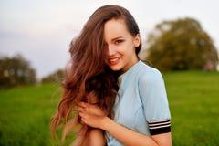 Mujer joven atractiva que disfruta de su tiempo afuera en parque de la puesta del sol Muchacha modelo con la presentación larga m foto de archivo
