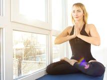 Mujer joven atractiva que ejercita y que se sienta en la posición de la yoga del loto, enfrente de la ventana fotografía de archivo