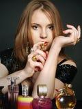 Mujer joven atractiva que elige aromas de la perfumería fotografía de archivo