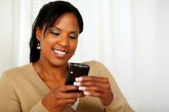 Mujer joven atractiva que envía un mensaje de texto fotografía de archivo libre de regalías