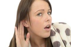 Mujer joven atractiva que es entrometida escuchando detras de las puertas una conversación Fotografía de archivo