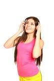 Mujer joven atractiva que escucha la música en un fondo blanco Imagenes de archivo
