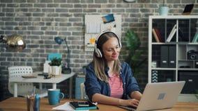 Mujer joven atractiva que escucha la música a través de los auriculares que bailan en el trabajo metrajes