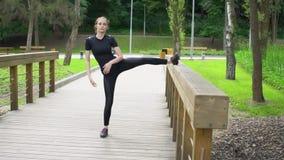 Mujer joven atractiva que estira las piernas en el puente de madera Hacer entrenamiento en el parque Cámara lenta metrajes
