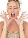 Mujer joven atractiva que grita o que dice en voz alta para la atención o la ayuda Fotos de archivo