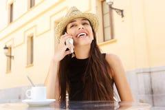 Mujer joven atractiva que habla en el teléfono móvil en el café Imagenes de archivo