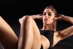 Mujer joven atractiva que hace crujidos durante entrenamiento Imagen de archivo