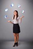 Mujer joven atractiva que hace juegos malabares con los iconos sociales de la red Foto de archivo libre de regalías