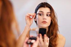 Mujer joven atractiva que hace maquillaje mientras que mira el espejo en cuarto de baño foto de archivo libre de regalías