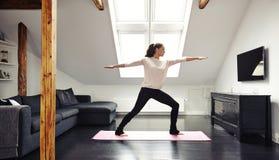 Mujer joven atractiva que hace yoga en casa Foto de archivo