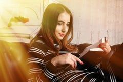 Mujer joven atractiva que lee un libro imagenes de archivo