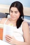 Mujer joven atractiva que lee un libro en cama Fotografía de archivo libre de regalías